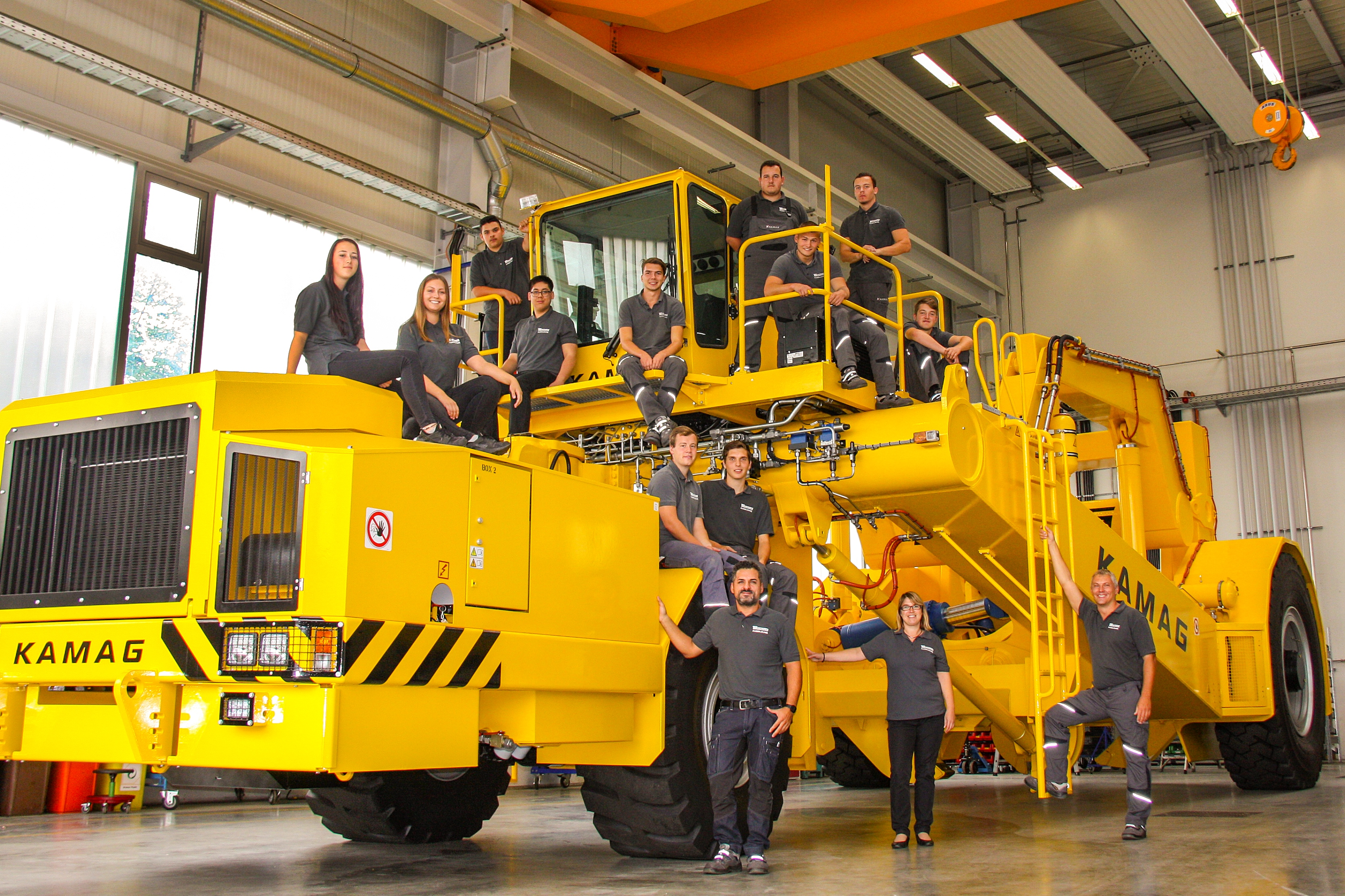 Kamag apprentices (including the new intake) together with their training supervisors explore a slab carrier (special vehicle for the transport of cast steel).